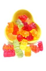 Haribo bear candies pouring out of yellow bowl.