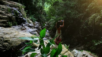 woman tourist taking photo with smart phone in jungle on