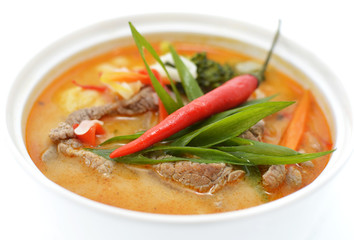 Asian spicy soup with beef in white bowl isolated