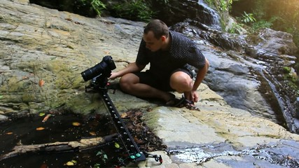 Caucasian tourist taking photos and videos of a waterfall in the