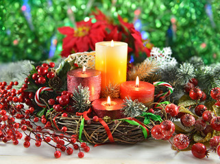 Christmas candles in wreath with decorations