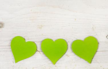 Holz Hintergrund weiß mit drei Herzen in apfelgrün