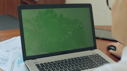 Close up of girl working at a laptop with green screen