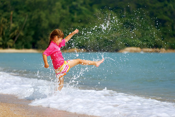Happy little girl enjoying holiday beach vacation.