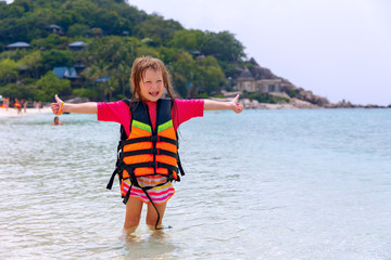 Little girl in a life jacket on the shores
