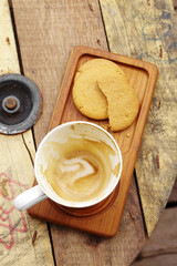 close up hot latte and cookie on wooden table
