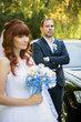 elegant groom posing with bride against wedding car