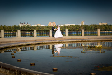 bride and groom holding hands and dancing at riverbank