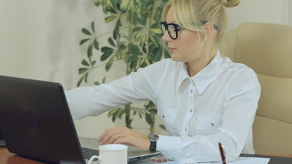 Attractive secretary is typing on the keyboard and then answers