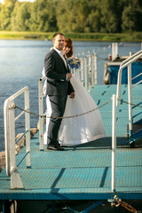 portrait of bride and groom hugging on pier on river
