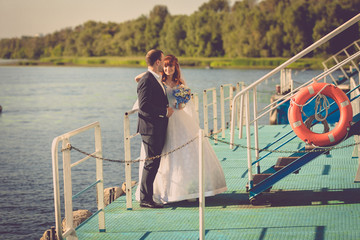 photo of beautiful bride and groom standing on pier on river