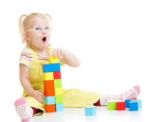 Funny kid in eyeglases making tower using blocks with letters