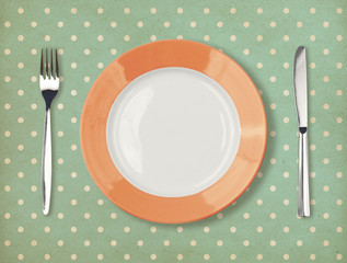 Retro plate with fork and knife on polka dot background