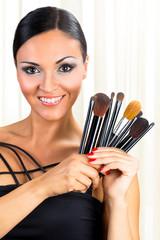 Beautiful woman represent  makeup brushes.