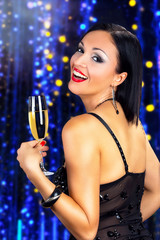 Attractive woman drinking champagne, against shiny background.