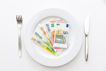 Geldverzehr, Scheine auf weißem Teller