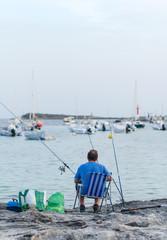 Man fishing in a bay near the boats.