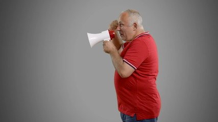 senior man with megaphone on a grey background.