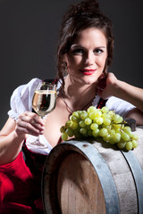 Junge Winzerin mit einem Glas Weißwein lehnt an Fass