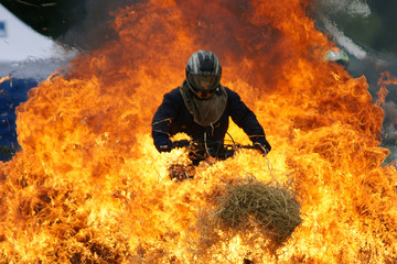 Stunt rider driving through fire