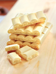 Bars of white porous chocolate on wooden background