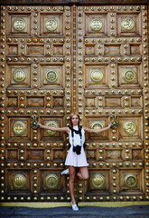 Female tourist girl with camera posing near vintage door