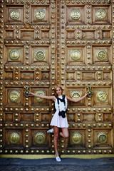Attractive teenager girl with camera posing near vintage door