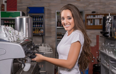 Waitress smiling in the coffee shop and making coffee.