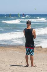 Boy looking at windsurfing coast in Medano