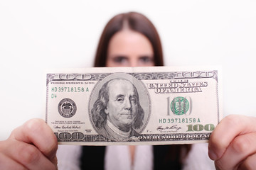 Woman holding dollar in front of her face.