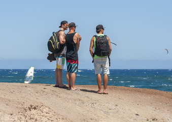 Boys looking at windsurfing coast in Medano
