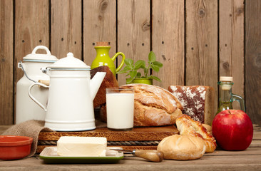 Fresh bread and butter and milk on wooden background