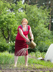 Mature woman watering plant