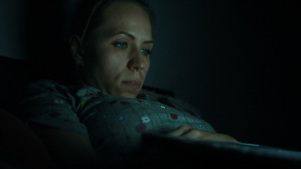 Woman lying with her laptop in night in the living room