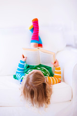 Little girl reading in white room
