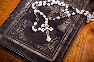 Rosenkranz mit Kruzifix auf schwarzer Bibel,