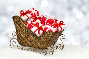 Christmas sleigh filled with gift boxes and twinkling background