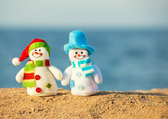 Two snowmans on sand