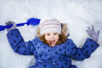 Little girl playing in the snow with a shovel.