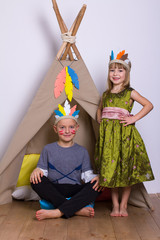 Girl and boy in carnival costumes indians studio