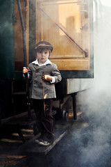 Boy, dressed in vintage coat and hat, standing on stairs of stea