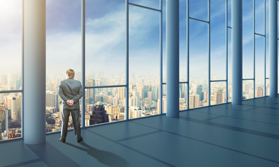 Businessman in the office with glass wals