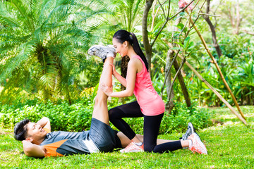 Asian coach helping woman with stretching exercises