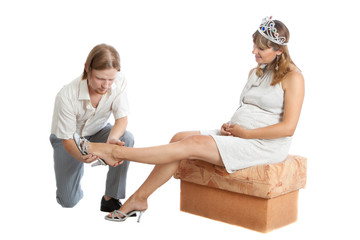 boyfriend helps a happy young pregnant woman