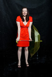 wet lass wearing red dress with umbrella stands under a rain poster