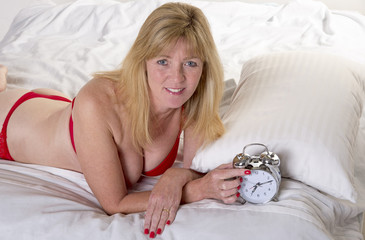 Woman laying in bed with alarm clock
