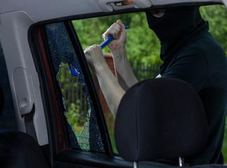 Burglar with crowbar breaking car window
