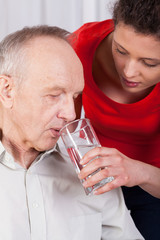Nurse helping disabled with drinking water