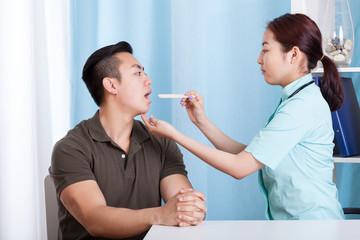 Asian man during throat examination
