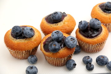 Blueberry Muffin with Blueberries in Background.
